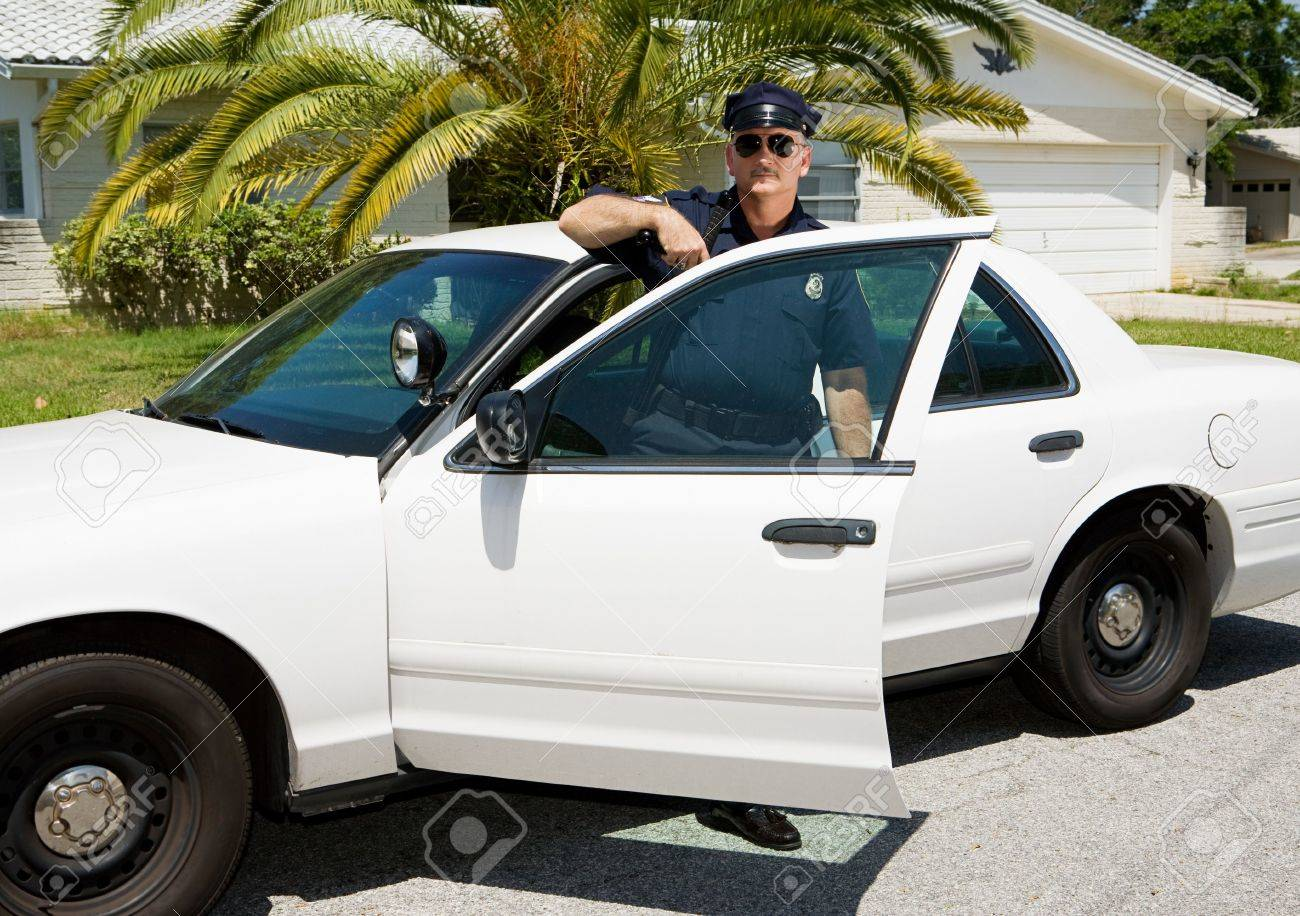 Uniformed law enforcement officer standing in the door of his police car. Stock Photo - 3010352