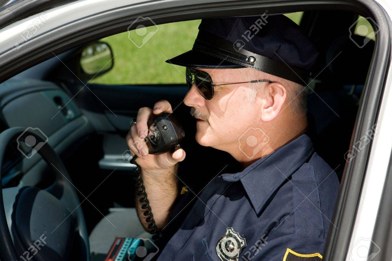 Police officer in squad car talking on his radio.  Closeup view. Stock Photo - 3010341