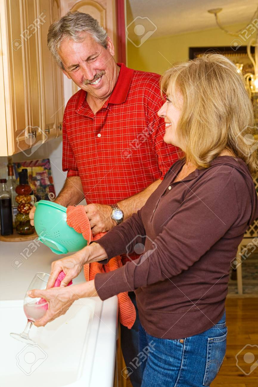 Beautiful mature couple cleaning the dishes together. Stock Photo - 3131938