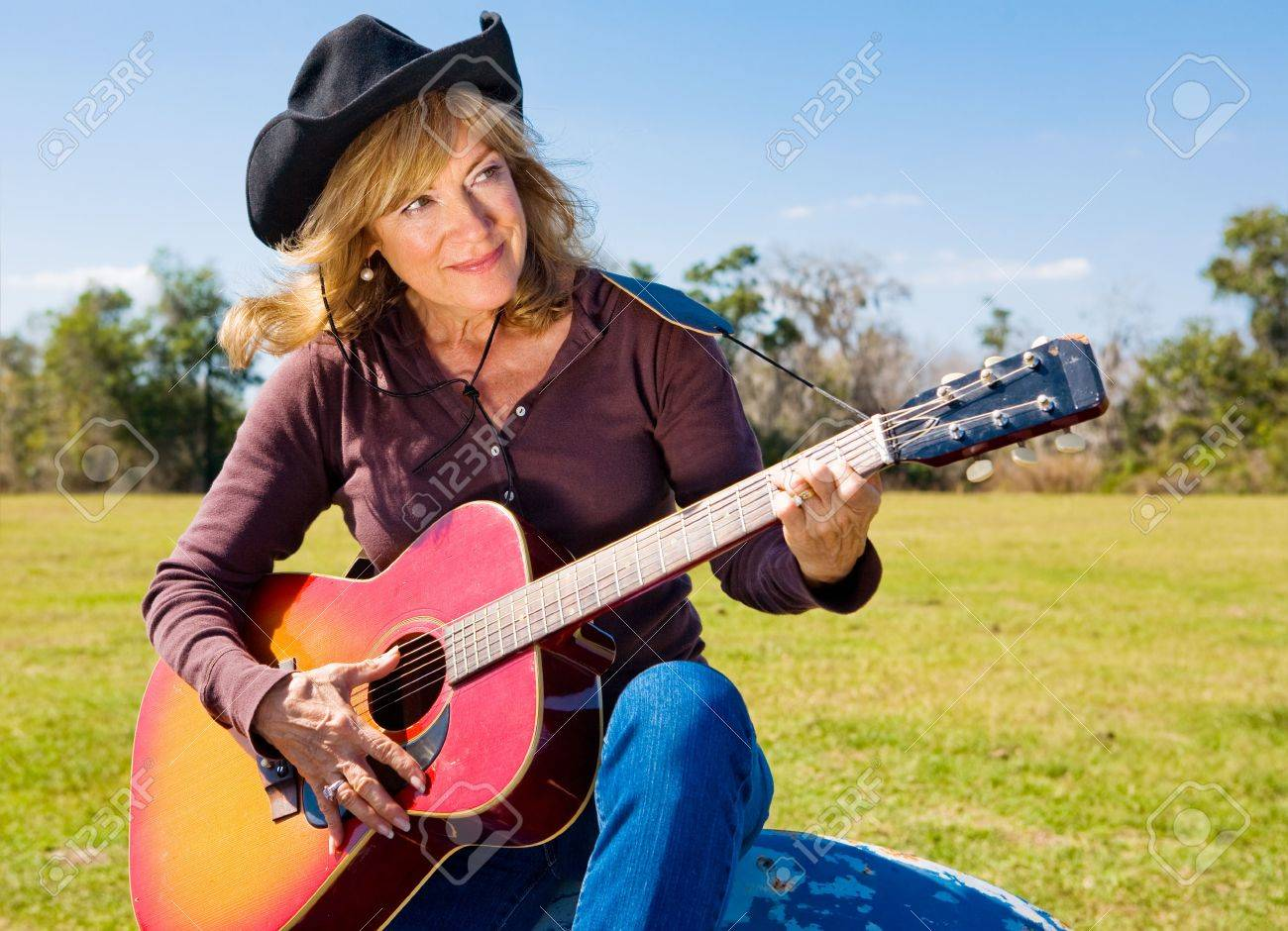 Beautiful mature singing cowgirl plays a song on her guitar. Stock Photo - 3206456
