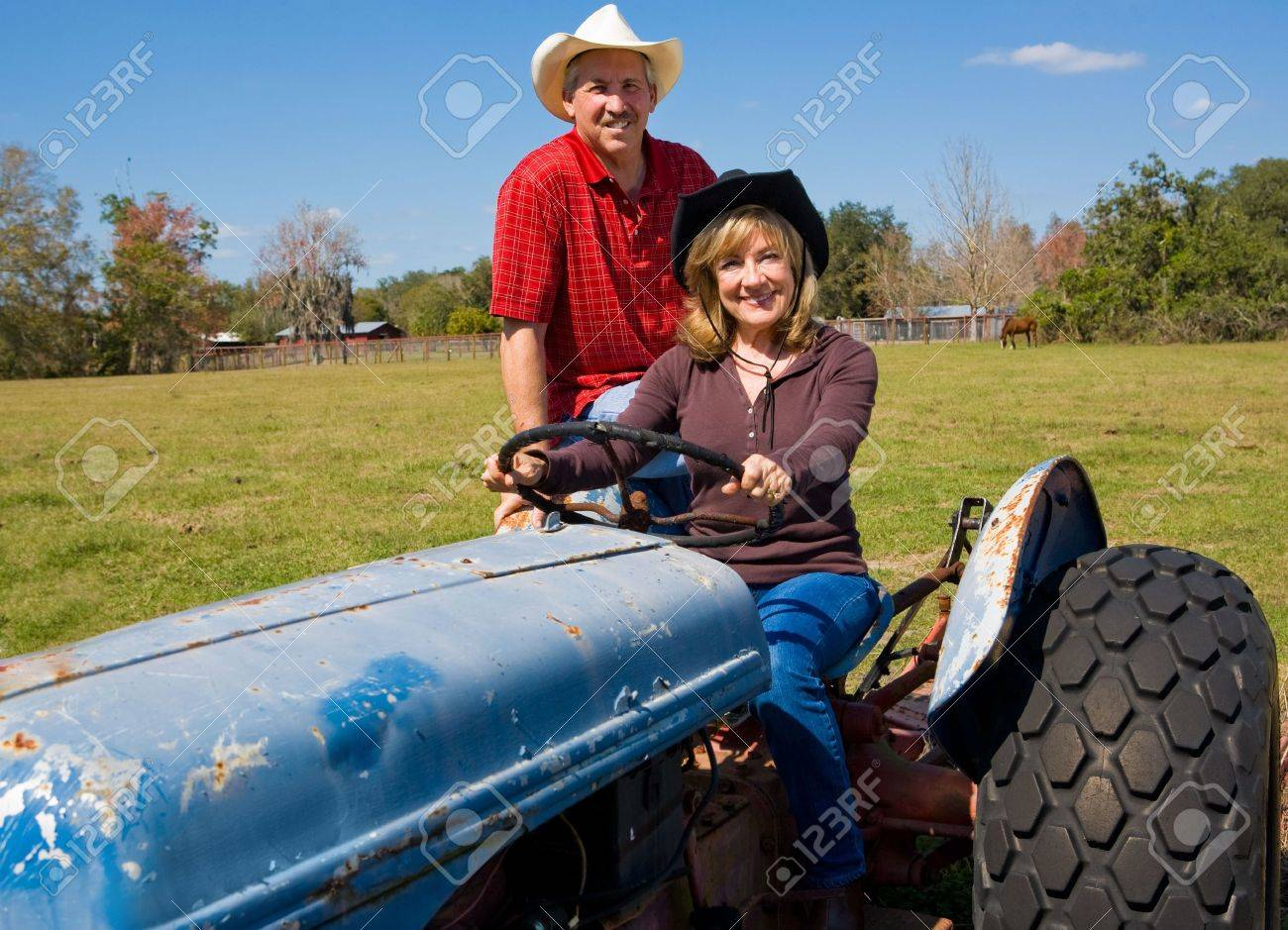 Beautiful mature couple riding a tractor on their farm. Stock Photo - 3206458