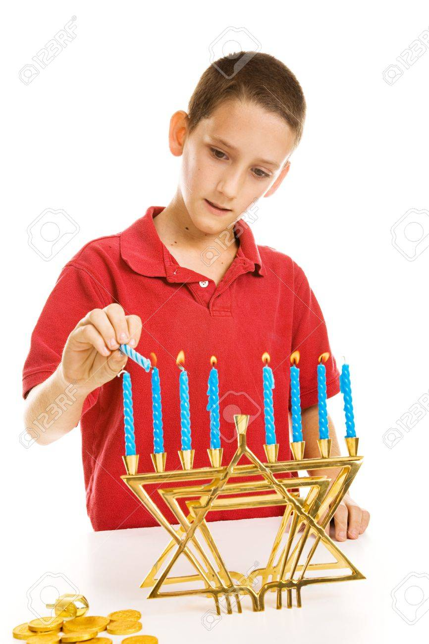 Young boy lighting the menorah for Hanukkah.  Isolated on white. Stock Photo - 3876396