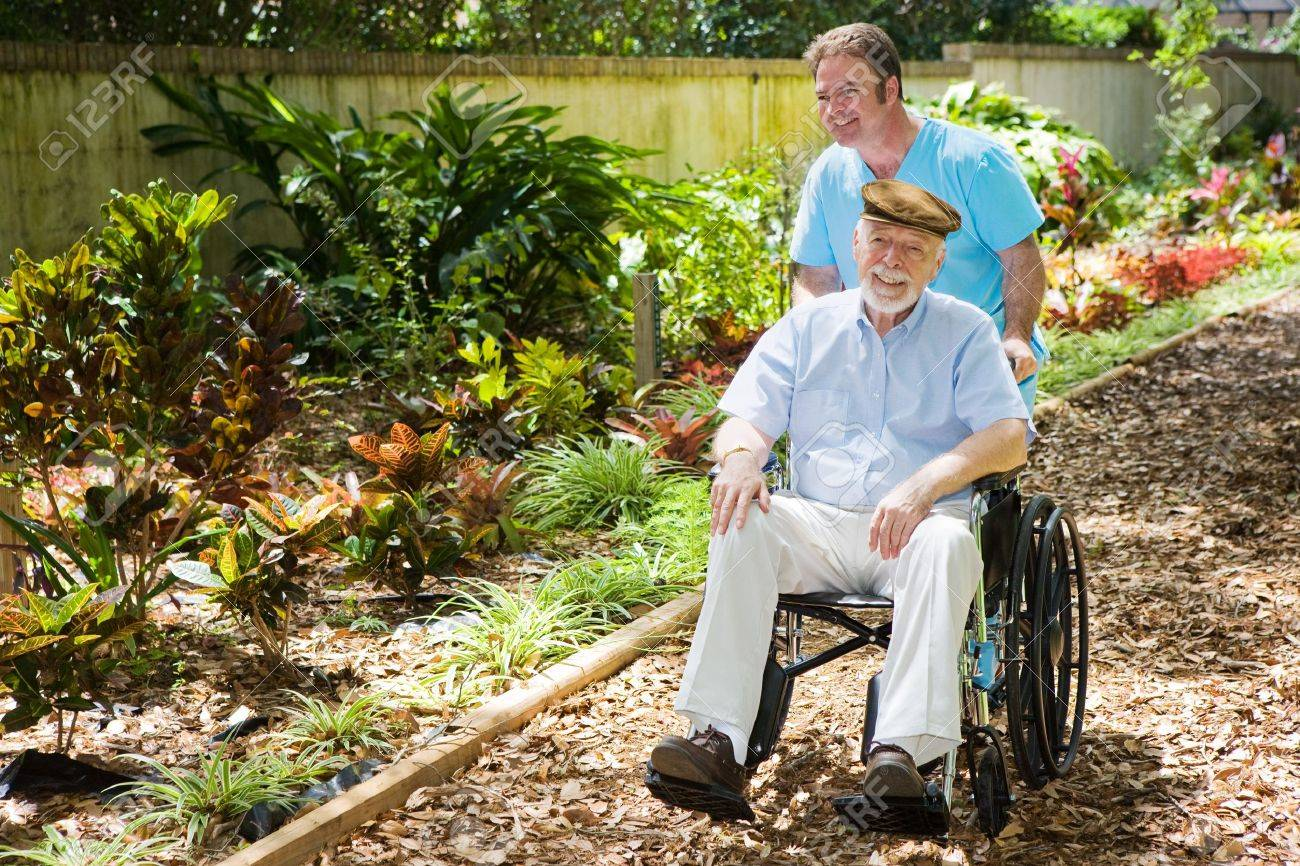Disabled Senior Man Being Pushed Through A Lovely Garden By His