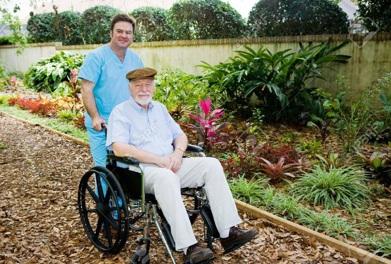 nursing home orderly takes a senior man for a walk in the garden stock photo. beautiful ideas. Home Design Ideas