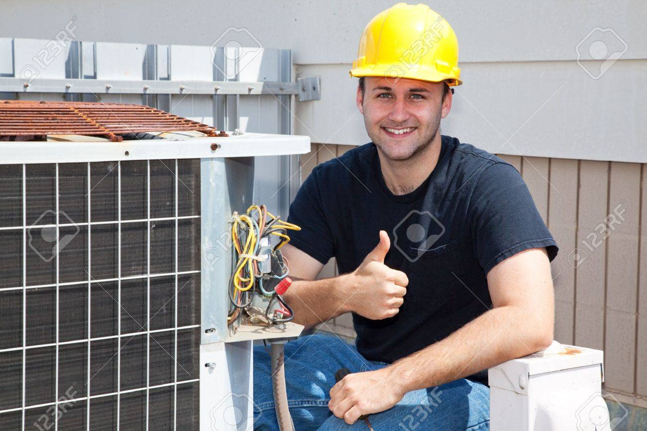 Air conditioning repairman working on a compressor and giving a thumbsup. Standard-Bild - 4531626