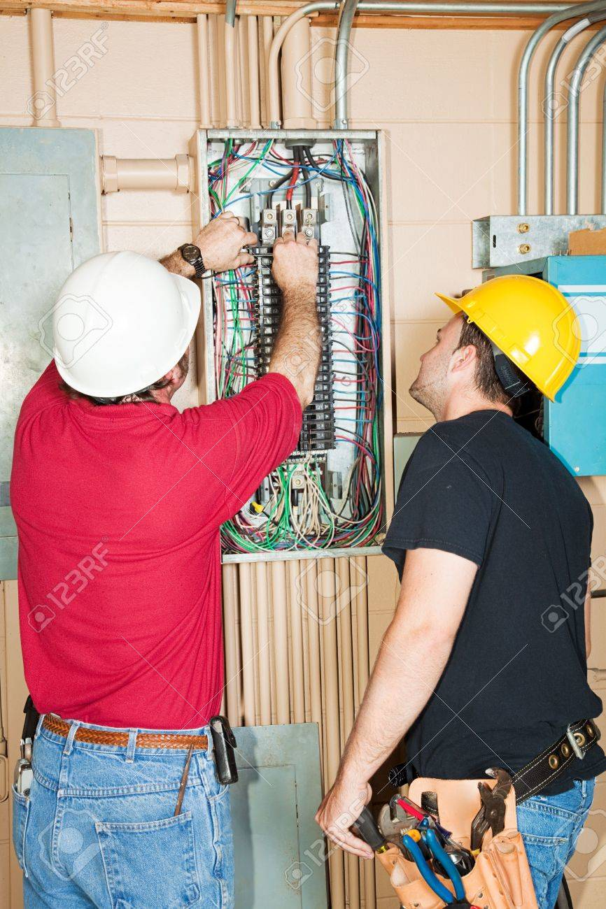 Electrician and apprentice changing out a faulty circuit breaker in an industrial panel. Stock Photo - 4685103