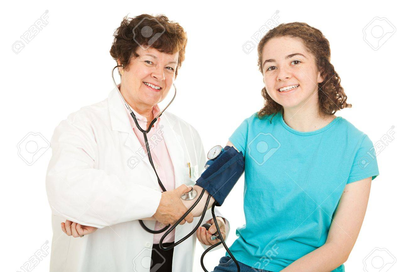 Friendly female doctor and her happy teenage patient, smiling as the doctor checks the girl's blood pressure.  Isolated. Stock Photo - 5002207