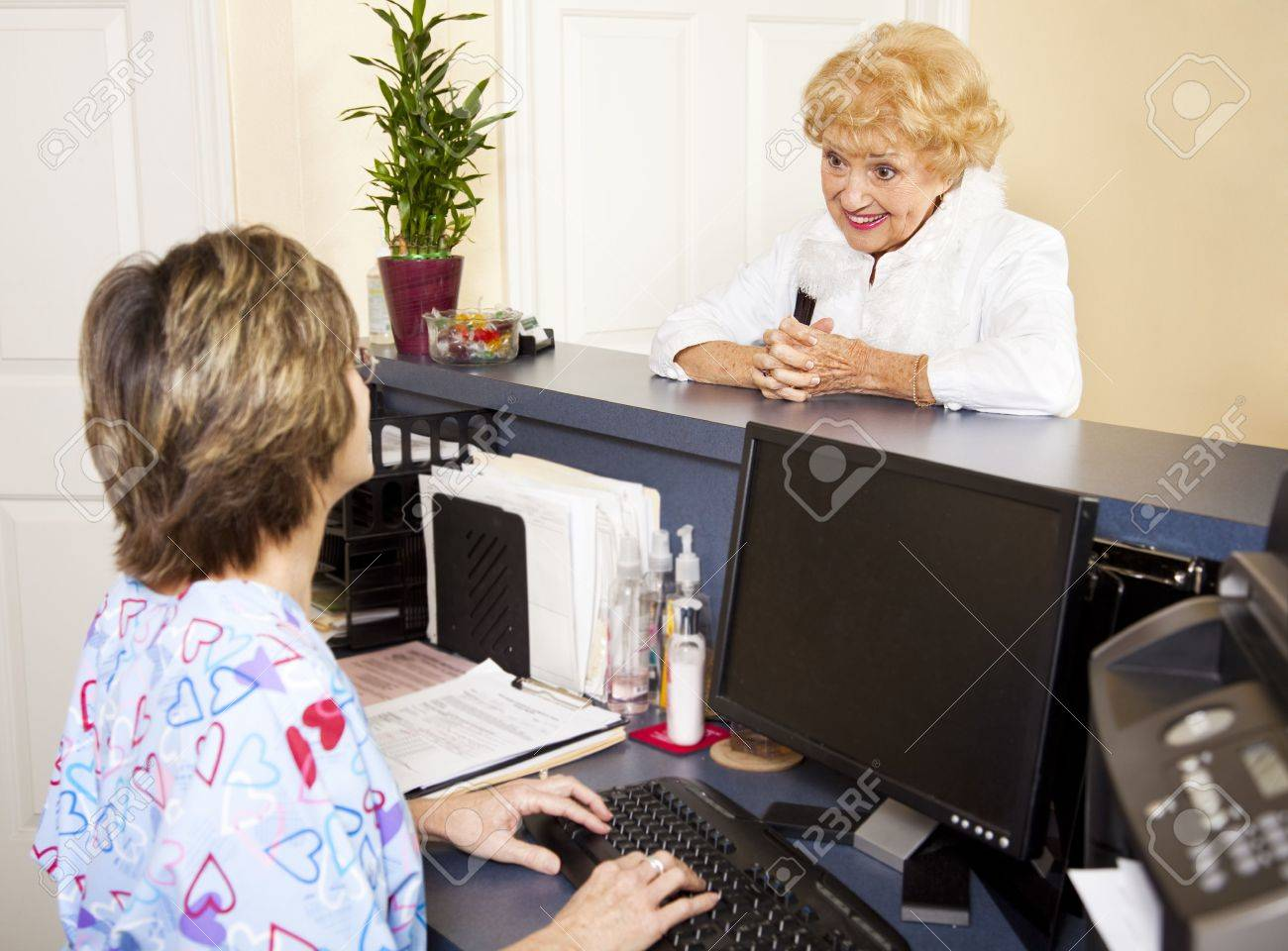 pretty senior lady checking in at the doctor s office reception pretty senior lady checking in at the doctor s office reception desk stock photo 6453339
