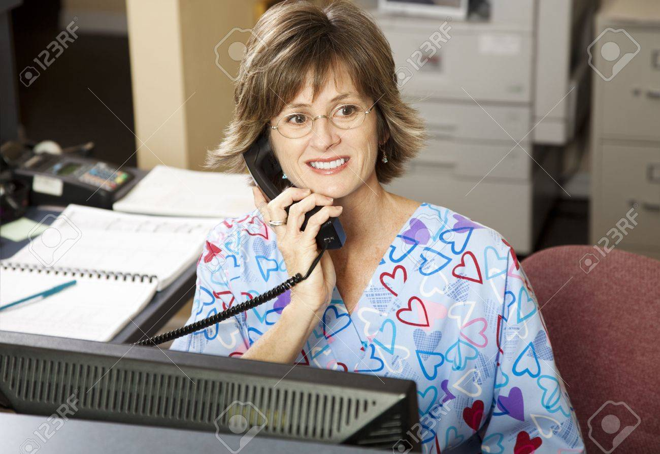 Busy medical receptionist working the front desk at a doctor's office. Stock Photo - 6453363