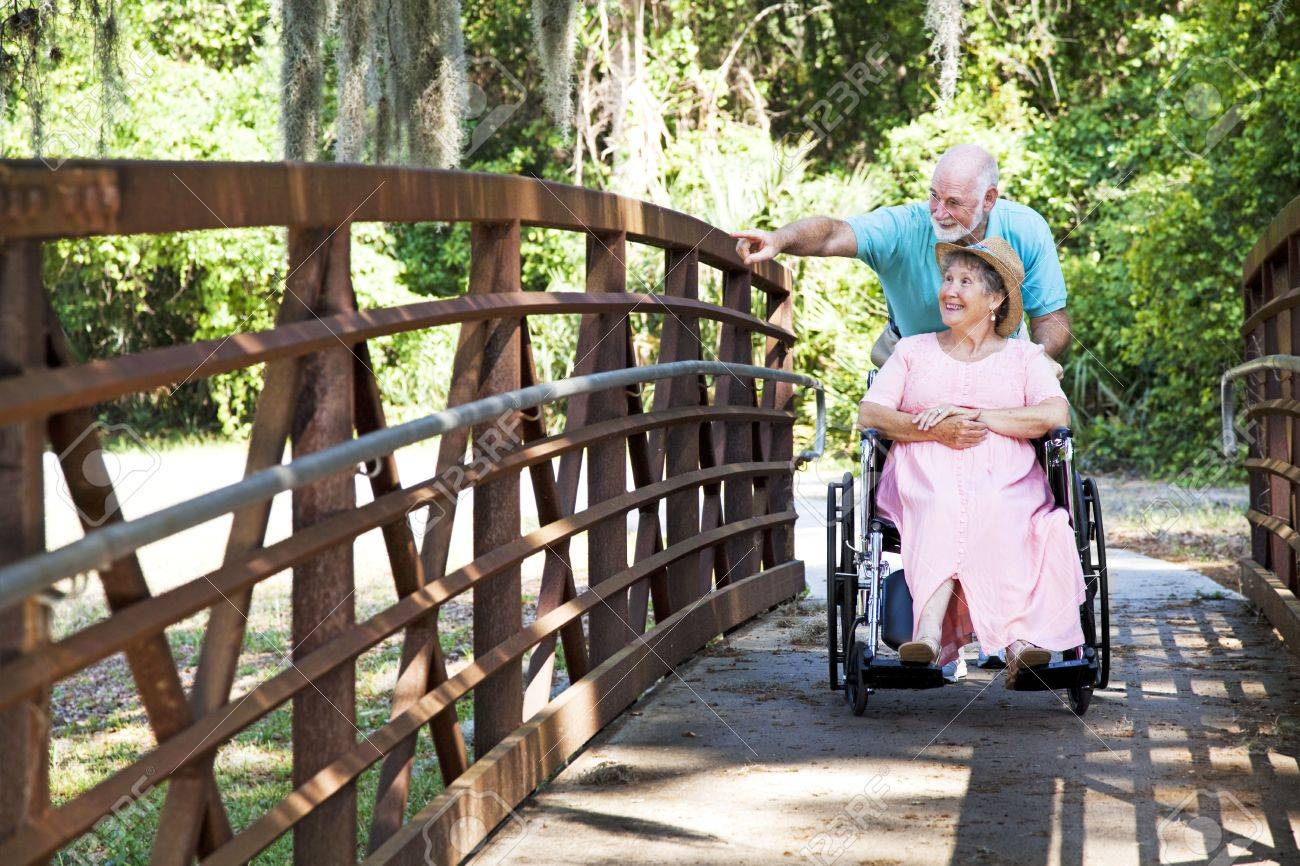 Senior man pushes his disabled wife's wheelchair through the park. Stock Photo - 7064282