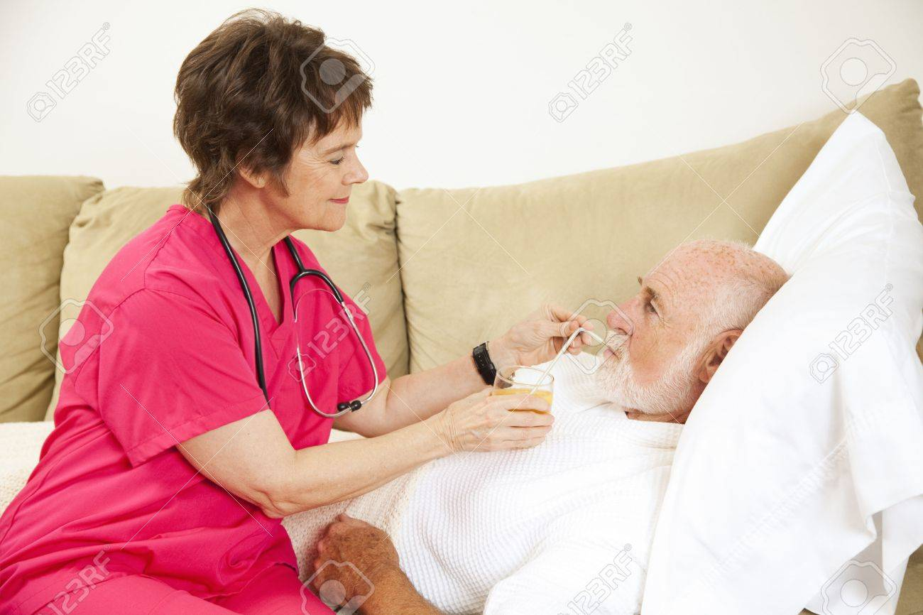 Home nurse helps elderly patient drink a glass of orange juice. Stock Photo - 7170572