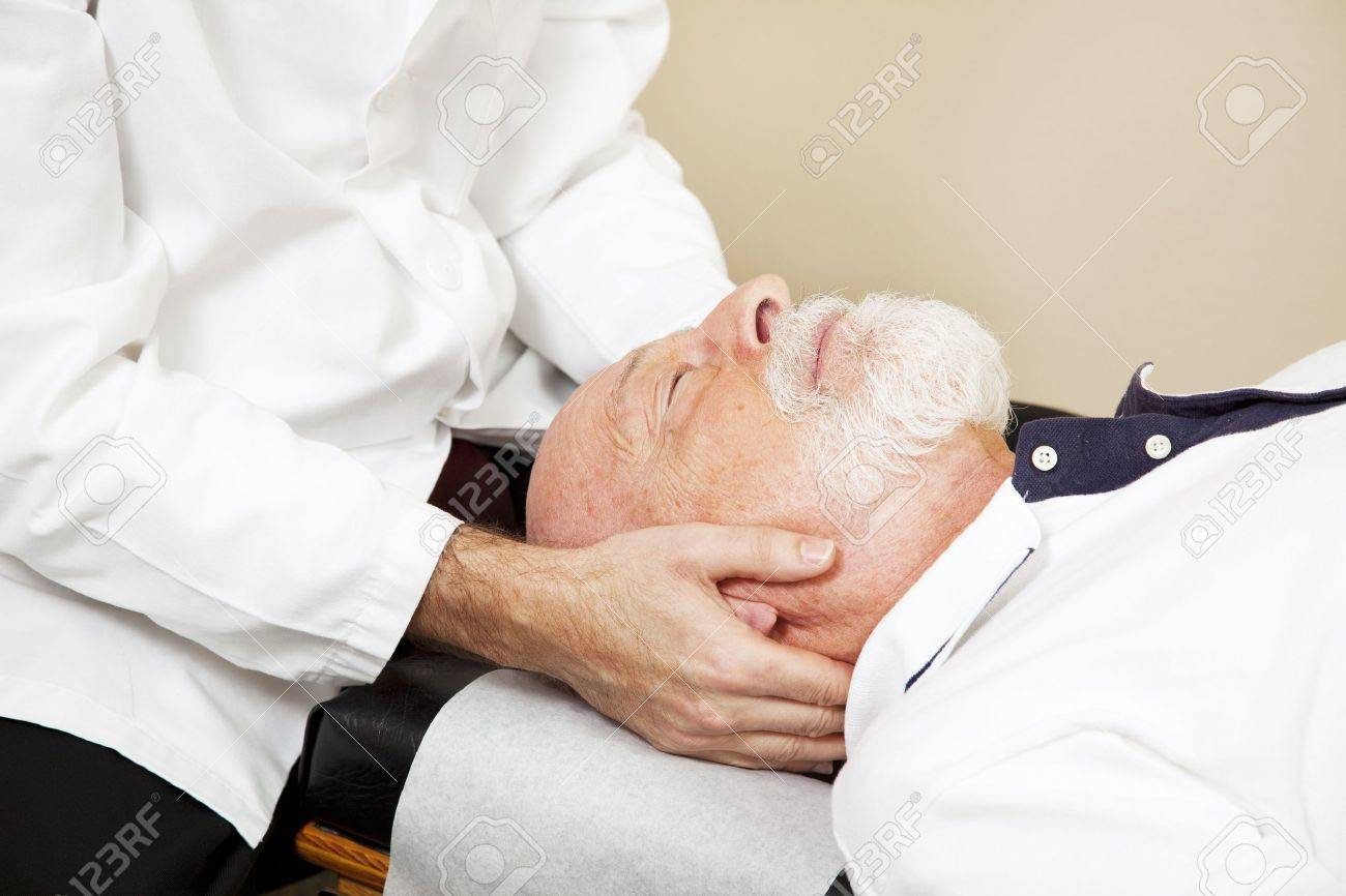 Closeup of a chiropractor adjusting a senior patient's cervical spine (neck). Stock Photo - 7281984
