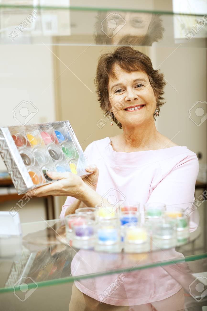 Store clerk or customer in a gift shop, holding up a package of candles. Stock Photo - 7477208