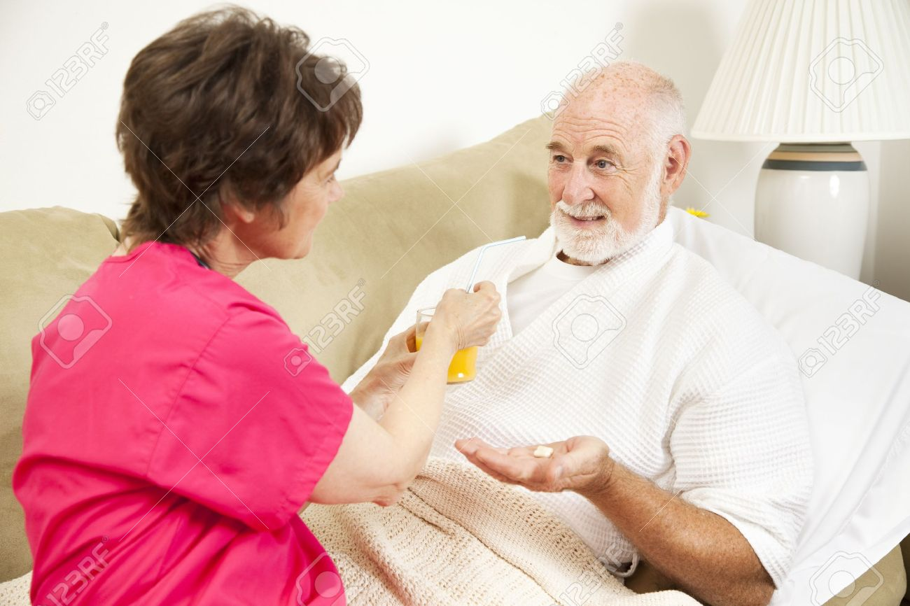 Home health nurse giving an elderly patient juice to make his medicine go down. Stock Photo - 7537816