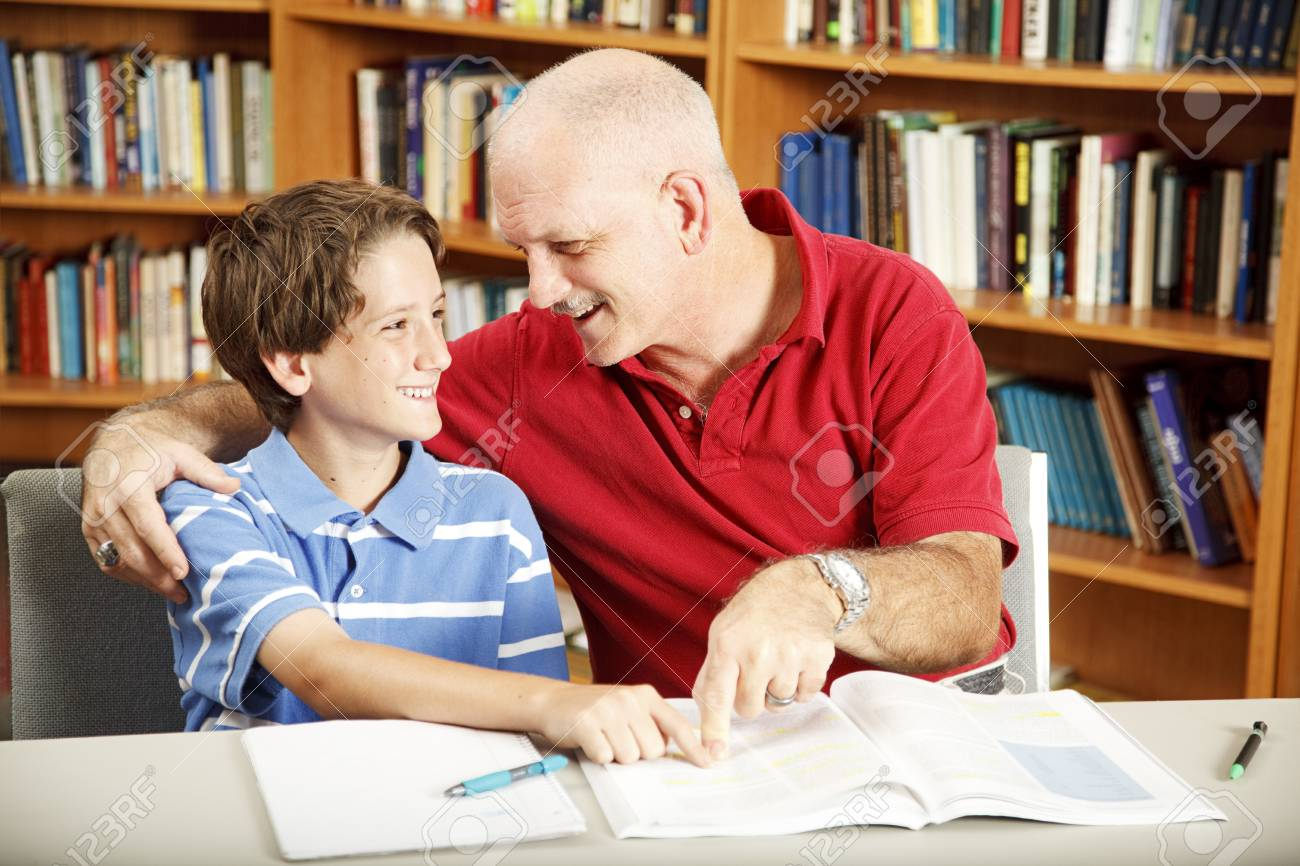 Cute school boy gets help with his homework from Dad. Stock Photo - 8174665