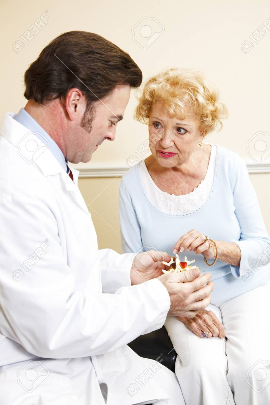 Chiropractor shows senior patient a model of the spine and discusses her treatment plan. Stock Photo - 8174651