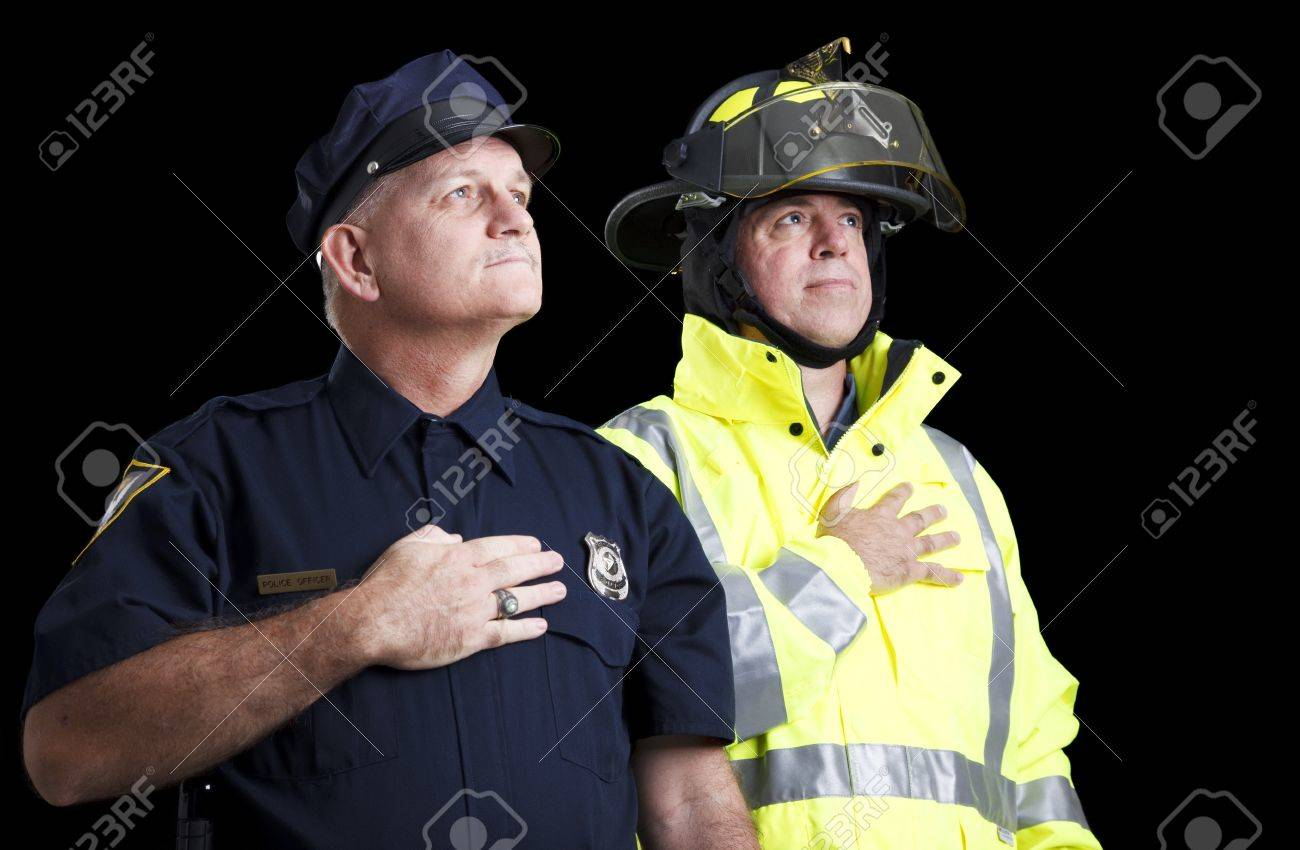 Police officer and fire fighter with their hands over their hearts as they say the Pledge of Allegiance. Stock Photo - 8264003