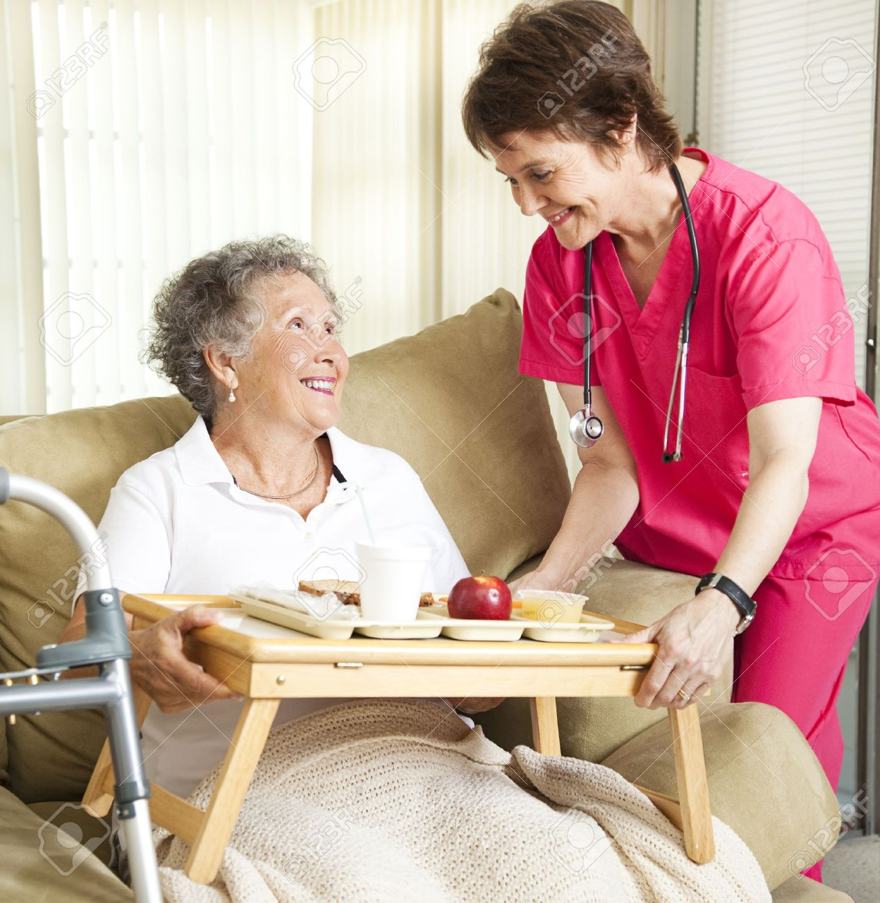 Retired senior woman in nursing home gets lunch from a caring nurse. Stock Photo - 8562736
