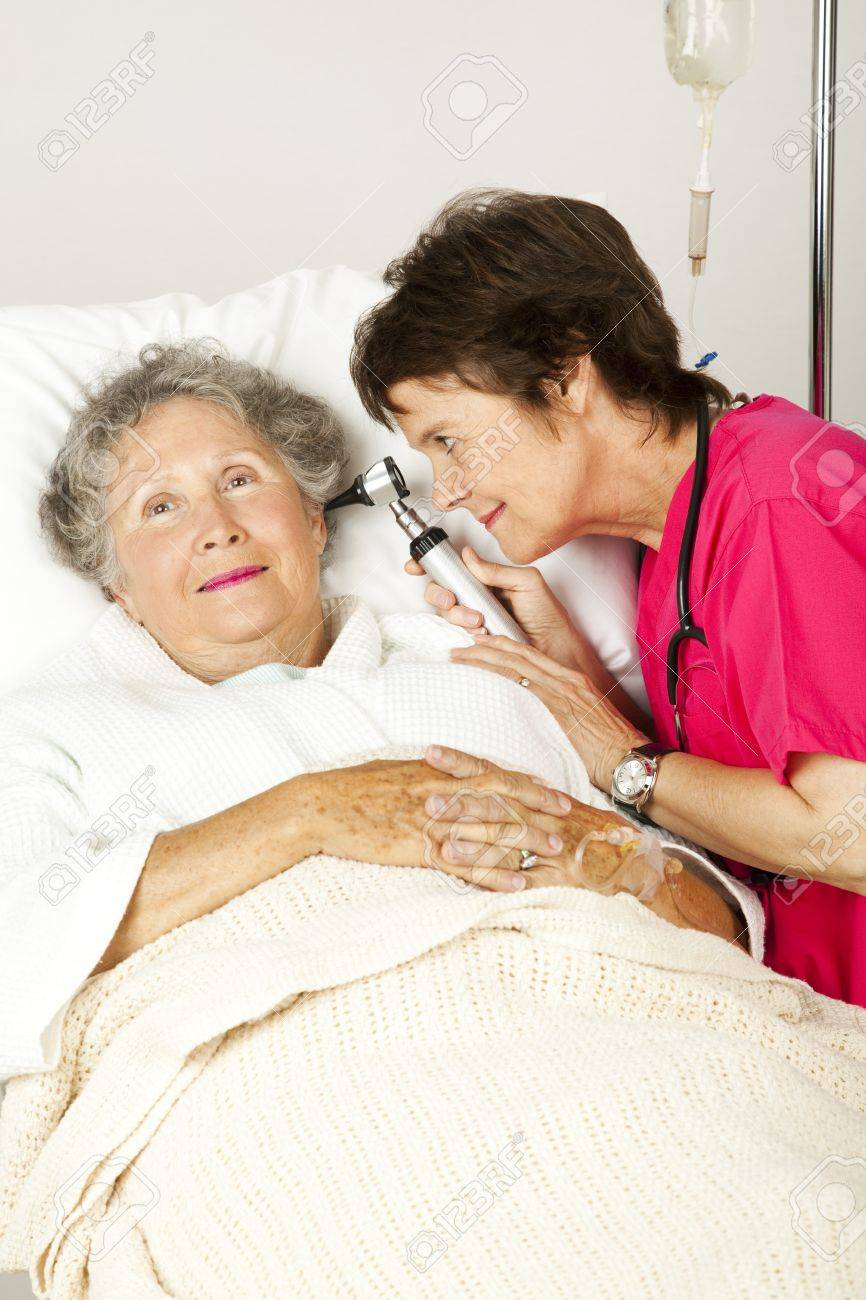 Hospital nurse checking a senior woman patient's ears with an otoscope. Stock Photo - 8687663