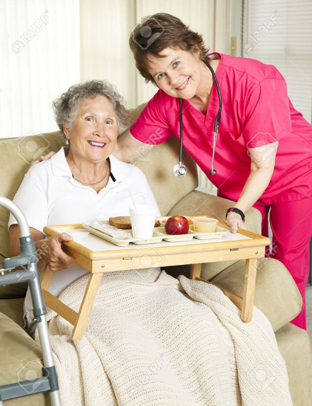 Caring nurse brings meal to home-bound senior woman. Stock Photo - 8728049