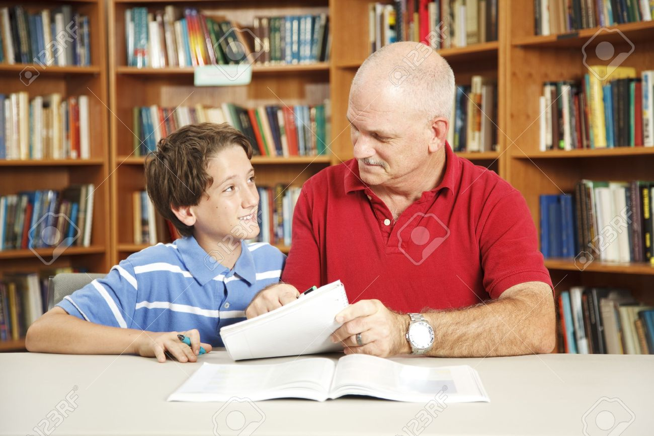 Father Or Male Teacher Tutoring A Young Student In The School ...