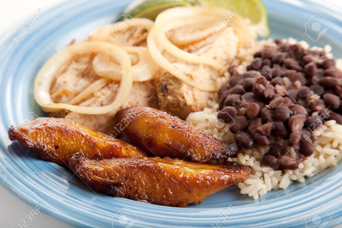 Closeup of Cuban dinner with focus on fried sweet plantains.  Marinated roast pork with black beans and rice complete the meal. Stock Photo - 9812332