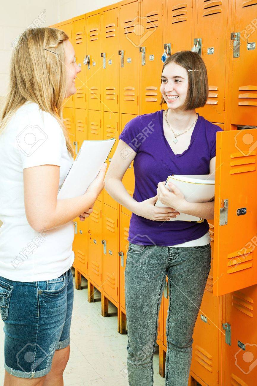 Two teenage girls chatting by their lockers in the school hallway. Stock Photo - 9969433