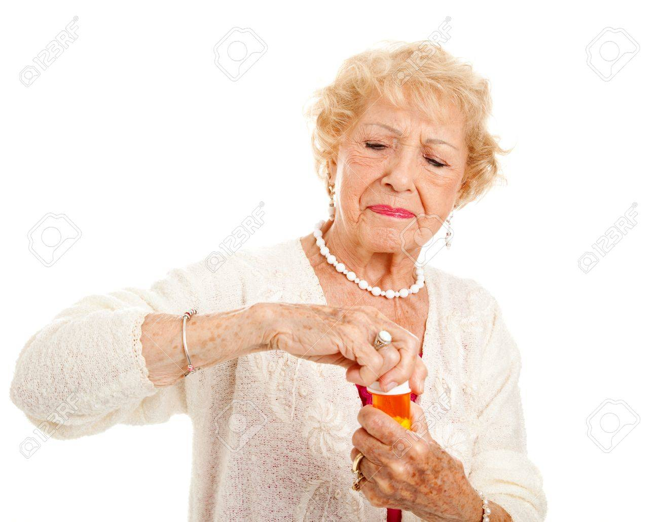 Senior woman with arthritis struggles to open a bottle of prescription medication. Stock Photo - 10104132