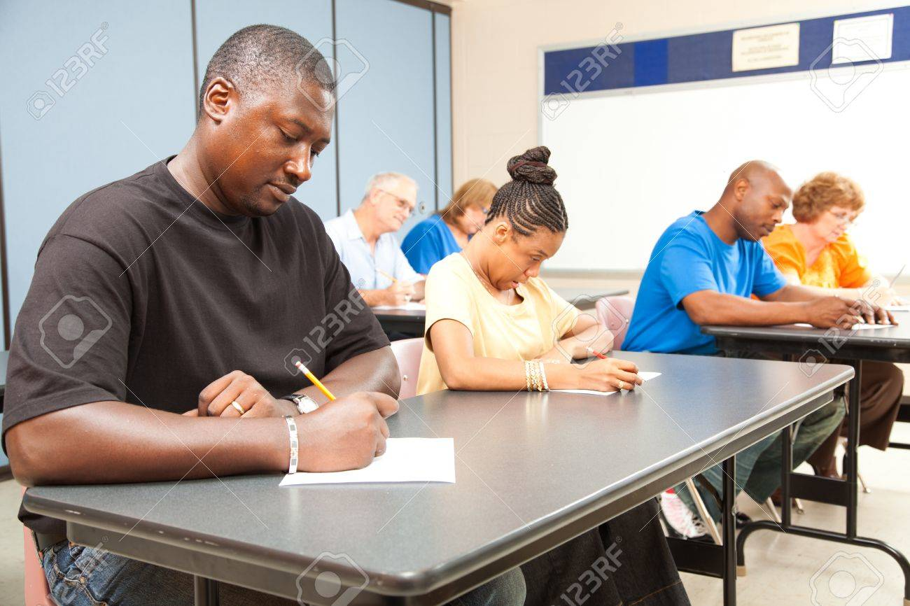 Class of adult college students taking a test.  Focus on guy in front left. Stock Photo - 10179261