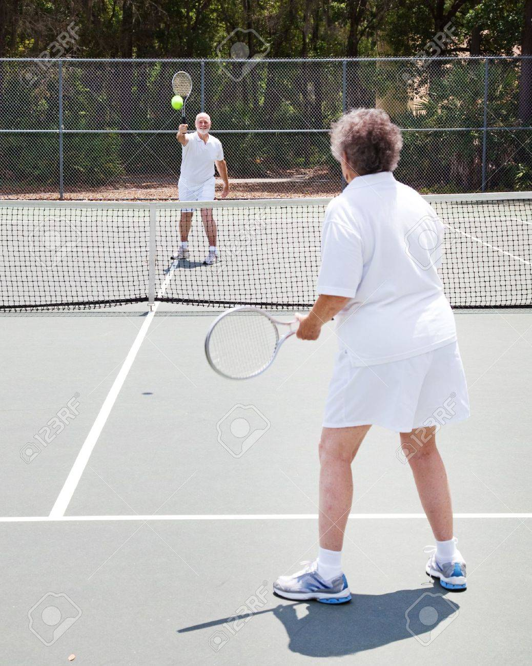 Active senior couple playing tennis together on an outdoor court Stock Photo - 10528919