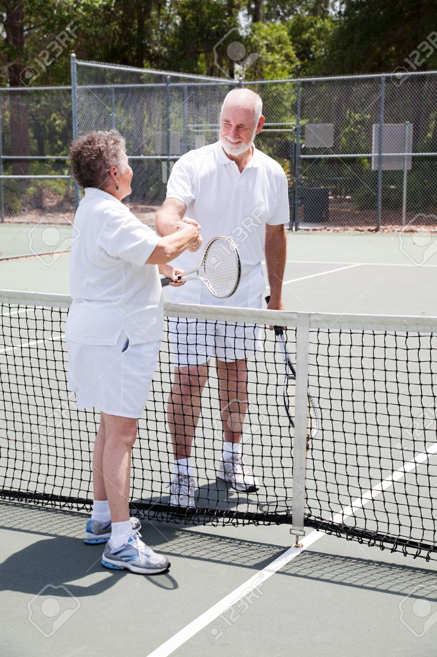 Active senior couple shakes hands over the tennis net. Stock Photo - 12165794