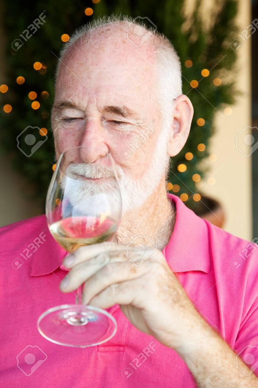 Senior man, enjoying the taste and aroma of a good glass of white wine. Stock Photo - 13425119