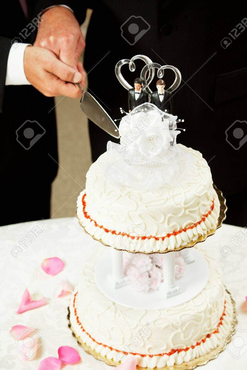 Closeup Of A Wedding Cake Topped With Two Grooms Being Cut By