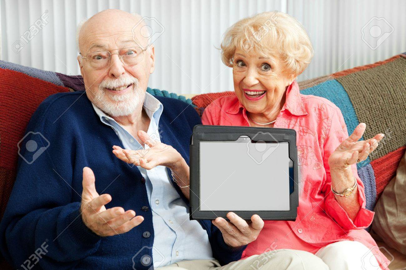 Confused senior couple holding their new tablet PC.  Blank computer screen ready for your text. Stock Photo - 13982960
