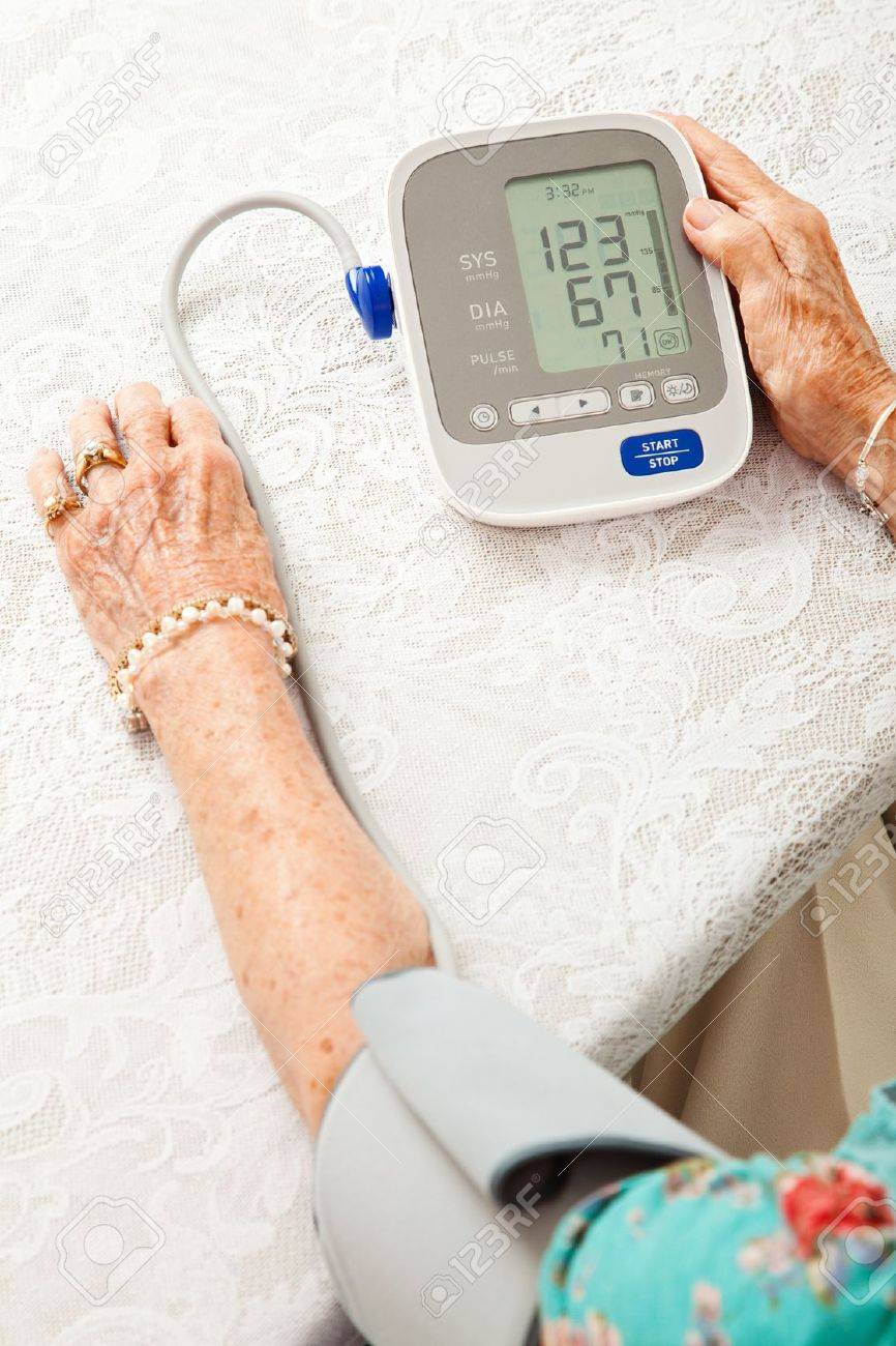 Senior woman using an automatic blood pressure cuff  to monitor her health at home Stock Photo - 14606678