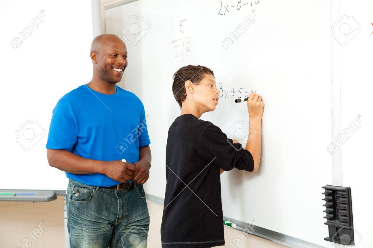 african american math teacher helping a student to pre algebra african american math teacher helping a student to pre algebra on the board stock