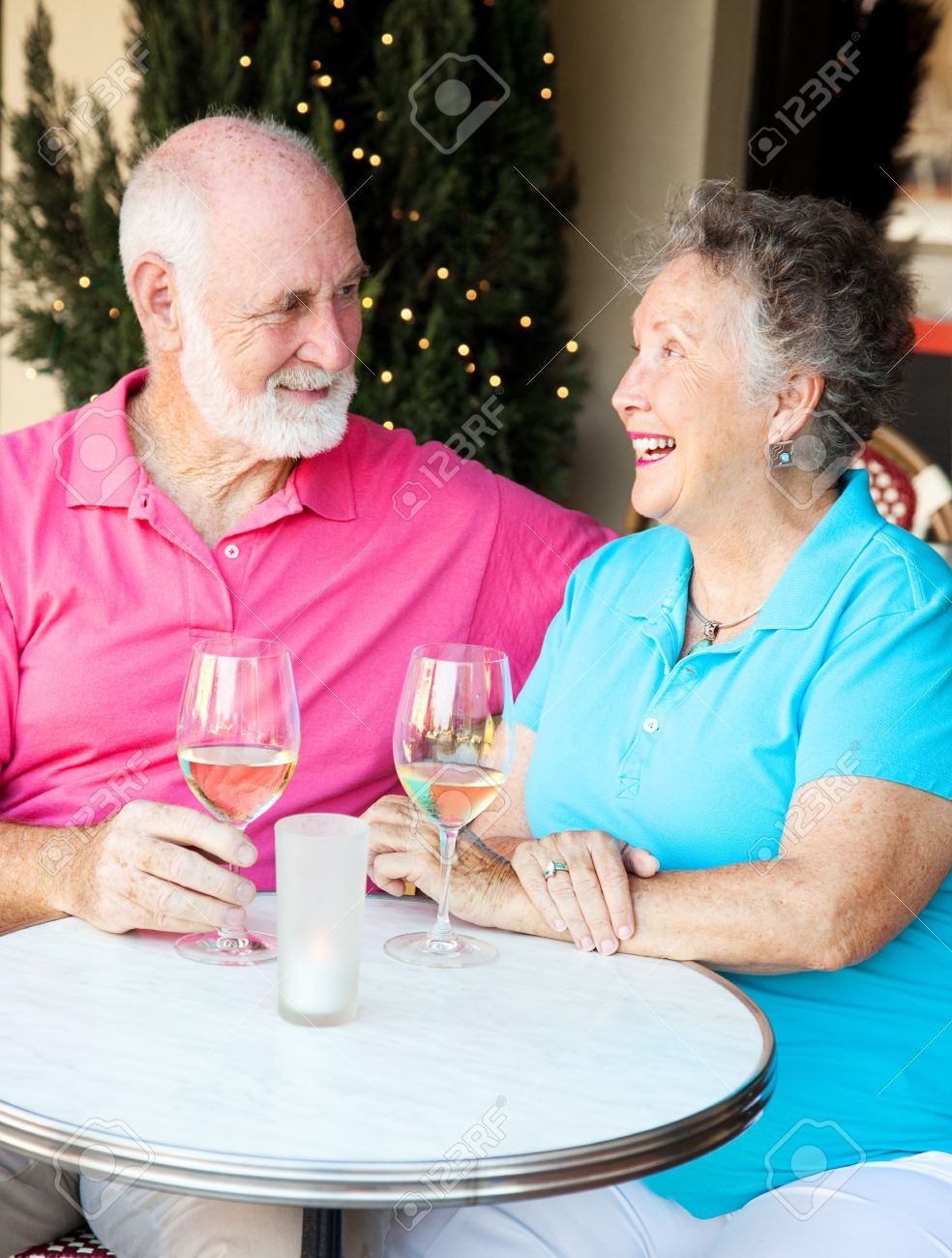 Senior couple enjoying a glass of wine and conversation at an outdoor cafe. Stock Photo - 14778816