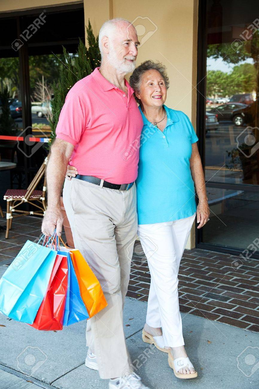 Happy senior couple walking at the mall with shopping bags. Stock Photo - 15563476