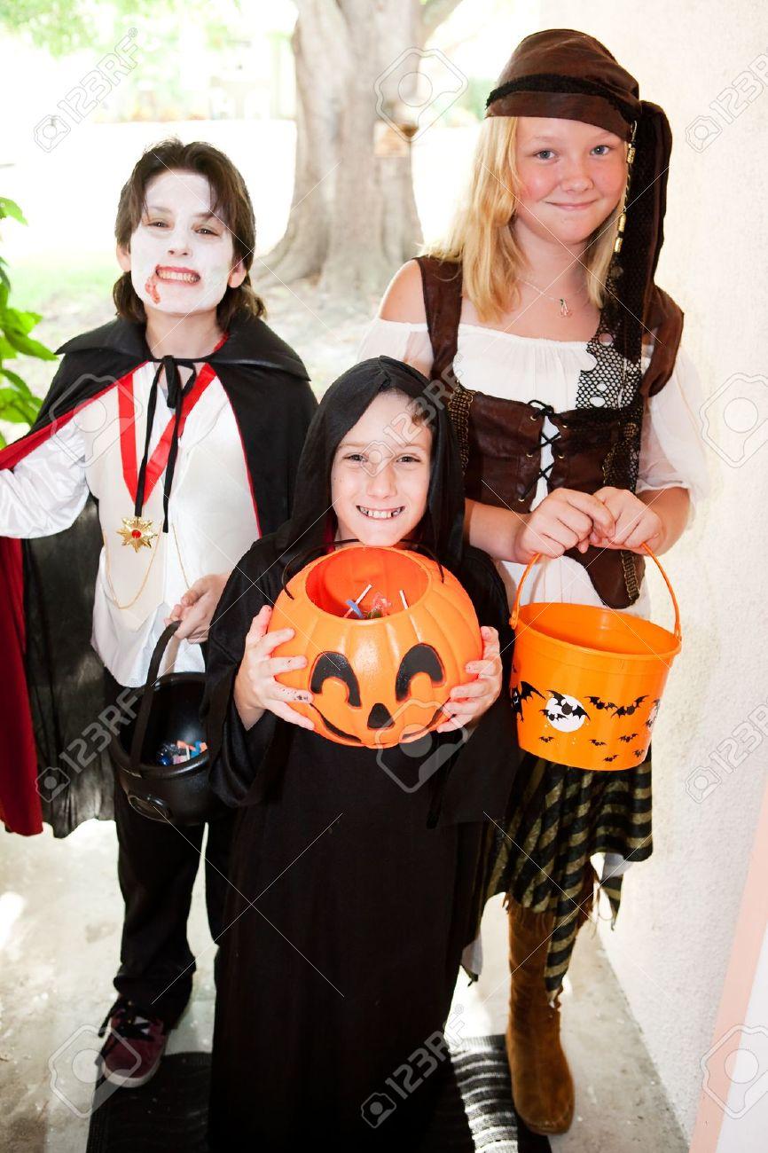three kids in halloween costumes going trick or treating doortodoor focus