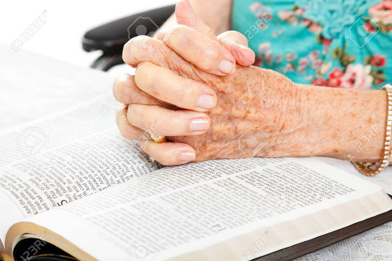 Closeup of senior woman's hands on bible, folded in prayer