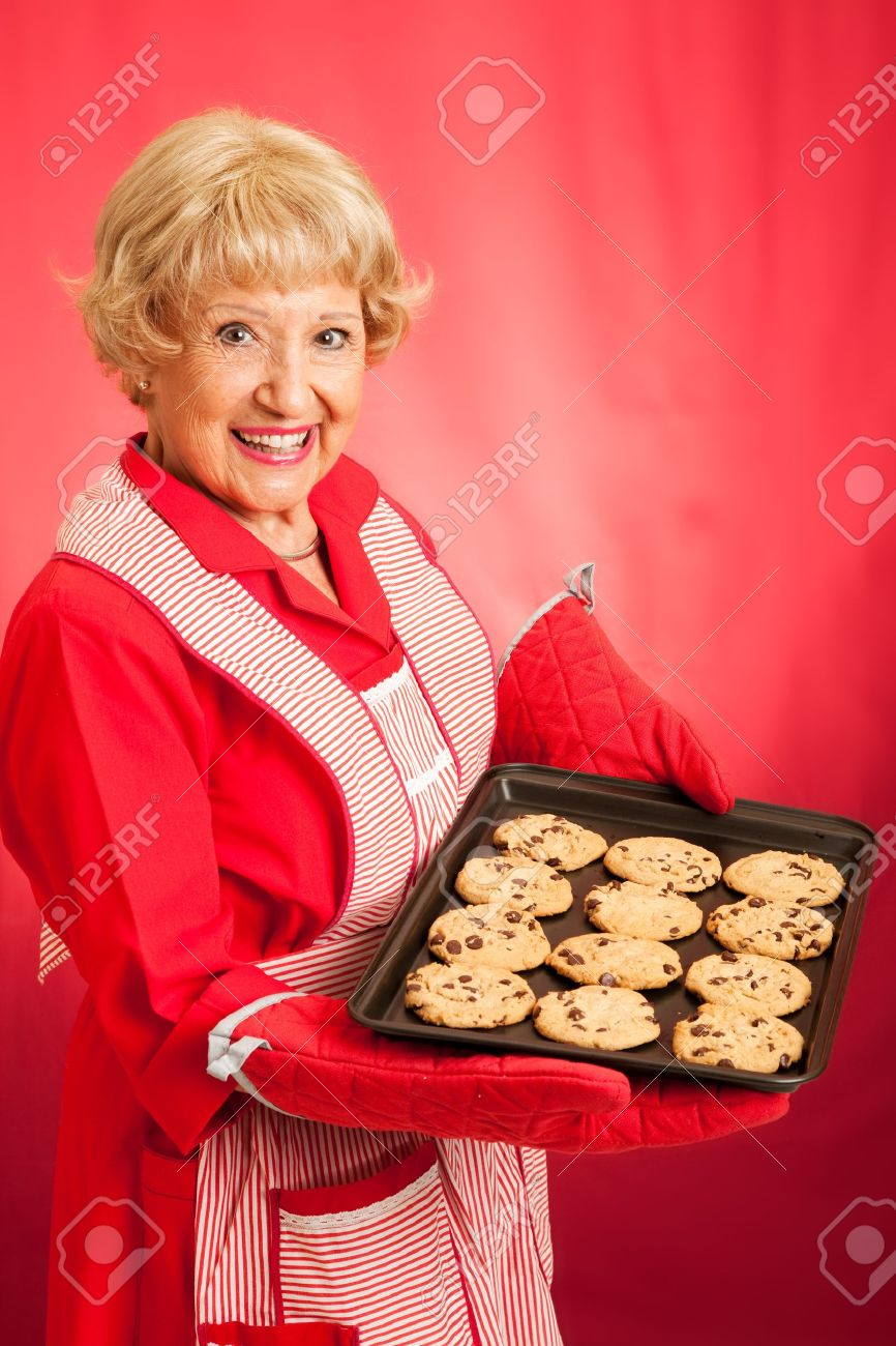 Sweet homemaker grandma holding a tray of fresh baked chocolate chip cookies.  Photographed in front of red background. Stock Photo - 16144067