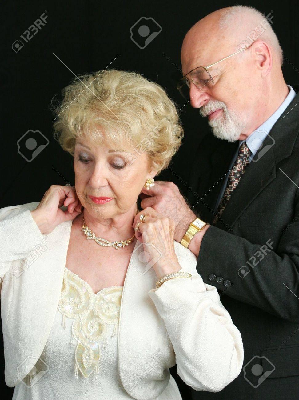 4368f59d4e066 写真素材 - 年配の男性が彼の妻を助ける彼の贈り物として彼女に与えている美しいダイヤモンドのネックレスをつけます。