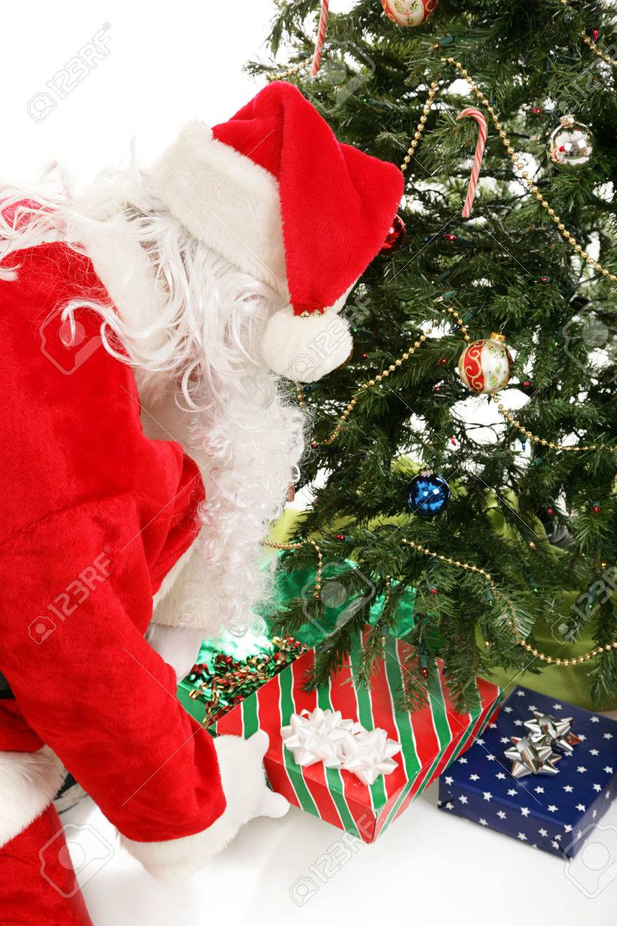 Santa Claus Leaving Gifts Under The Christmas Tree. Stock Photo ...