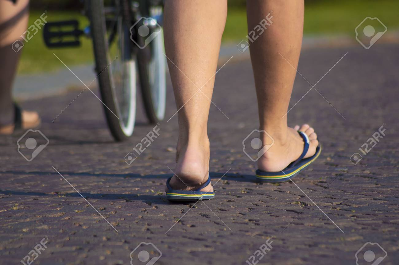 4d5c14b3f4d67 Girl with flip flops walking on the street of como city Stock Photo -  79876241