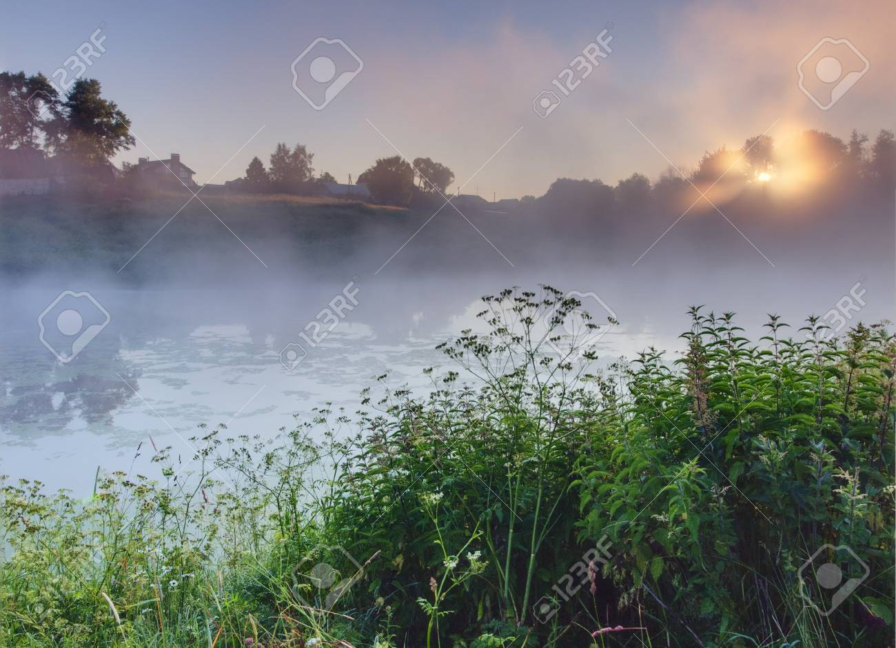 Rural early morning sunrise with lake, fog and russian church