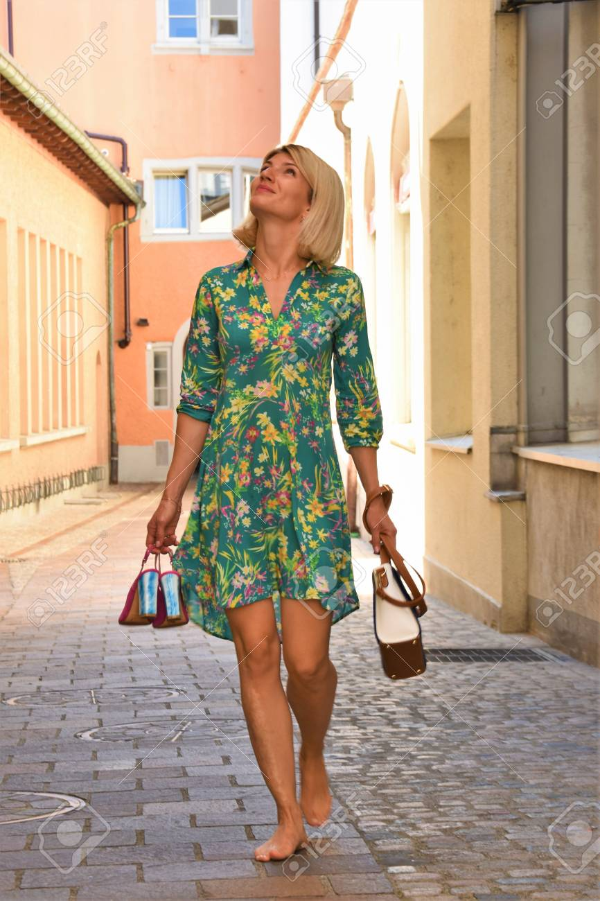 https://previews.123rf.com/images/lisica66/lisica661807/lisica66180700025/105378747-young-woman-walking-barefoot-on-the-street-and-looking-up.jpg