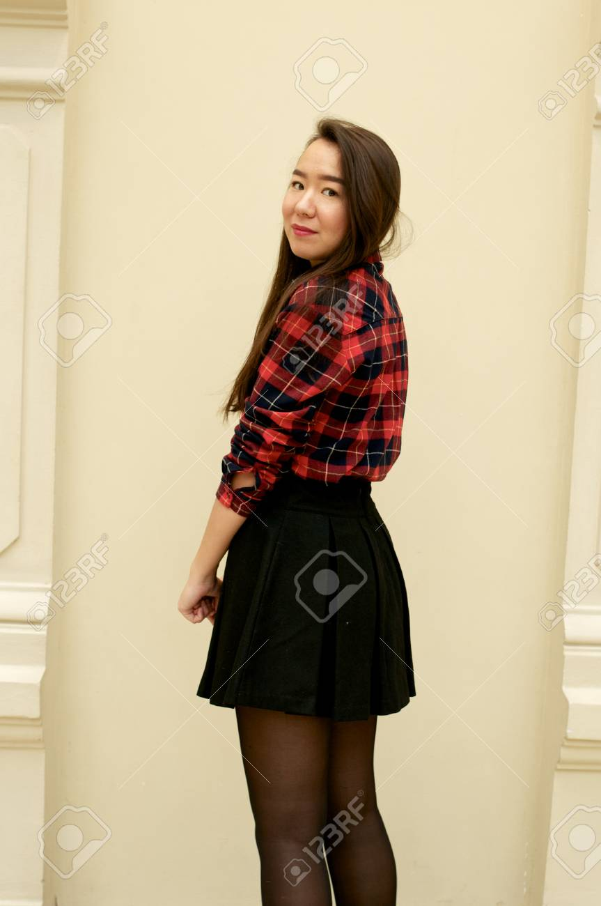 49e9e86a Girl half-turned to the camera in red shirt and black skirt Stock Photo -