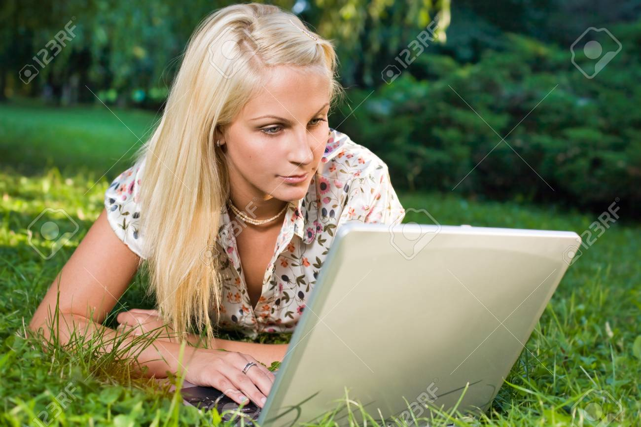 Beautiful young blond using laptop outdoors in nature. Stock Photo - 9310550