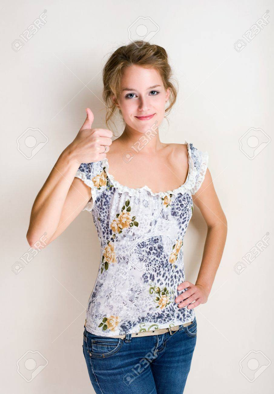 Half figure portrait of a cheerful fashionable young blond woman showing thumbs up. Stock Photo - 10771745