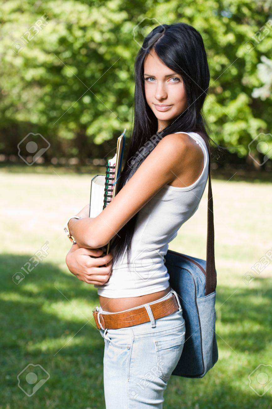 Portrait of an attractive young brunette student outdoors with exercise books. Stock Photo - 15005468